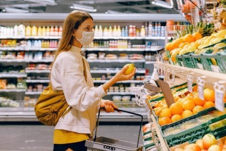 A masked woman shopping for produce during the COVID-19 pandemic. Retail and grocery consulting are of utmost importance during these uncertain times